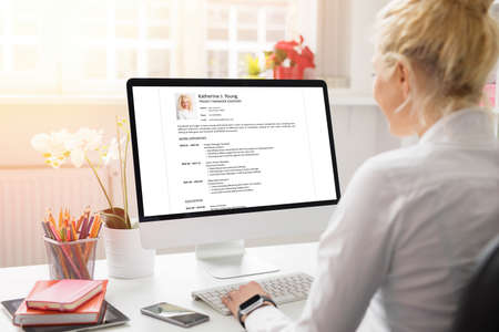 Woman creating her CV on computer. All contents in document are made up.