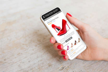 Woman shopping online on her phone for new red high heels Banque d'images