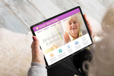 Senior woman looking at senior care facility website on tablet computer