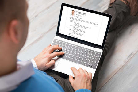 Man creating his CV on laptop. All contents in document are made up. Stock fotó