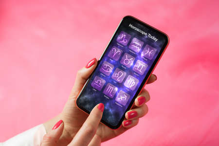 Person reading daily horoscope on mobile phone