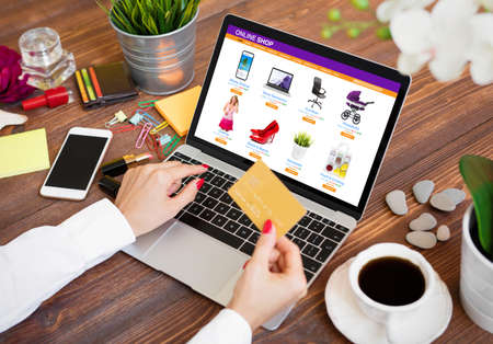 Woman shopping online on laptop and paying for purchased goods by credit card