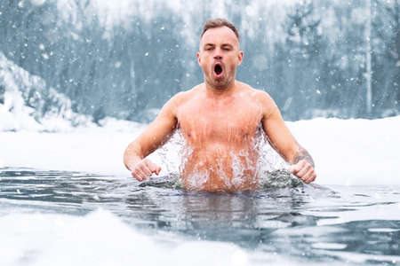 Man jumping in cold water in winter