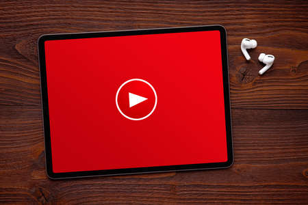 Play button on the screen of tablet and wireless earphones on dark wooden surface