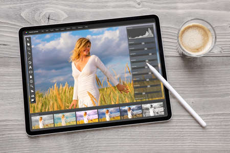 Concept of digital photo editing on tablet computer with wireless stylus pen 免版税图像