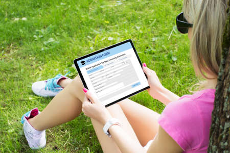 Girl submitting online admission form on tablet while sitting outside