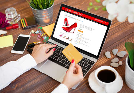 Woman buying new high heel shoes online and paying for purchase by credit card
