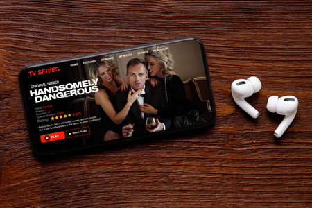 TV series and movies streaming app on mobile phone with wireless earbuds on table