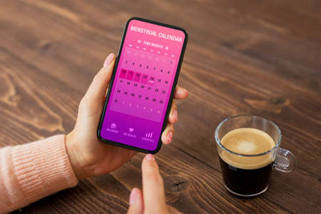 Woman using menstrual calendar app on mobile phone