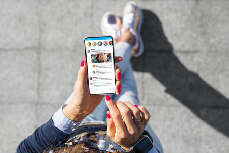 Woman using social media microblogging app on her phone