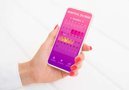 Woman using menstrual calendar app on phone