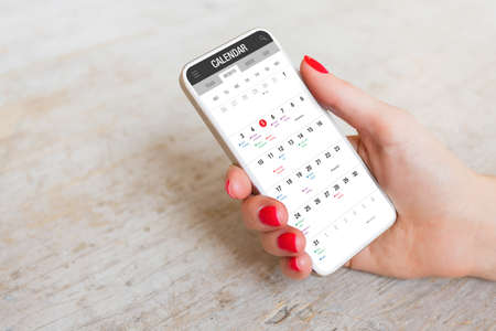 Woman using calendar app on mobile phone 免版税图像