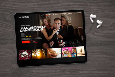 Sample TV series and movies streaming app on digital tablet and wireless earbuds on the table.