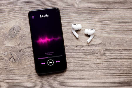 Music streaming app on mobile phone and wireless earbuds 免版税图像