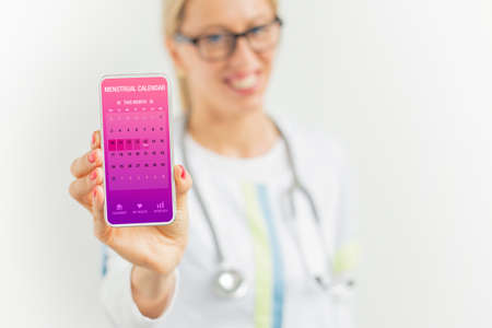 Doctor suggesting to use menstrual cycle tracking app on phone 免版税图像