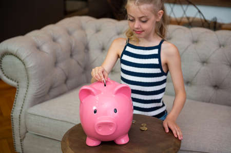 Girl saving money in piggy bank