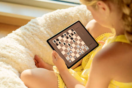 Girl playing chess online on tablet computer
