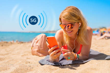 Woman using mobile phone on the beach, concept of 5G technology for fast wireless internet connection