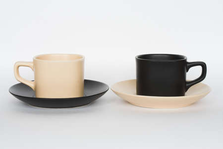 work took: Two coffee cups opposite each other - beige and black, with changed saucers, isolated on white Stock Photo
