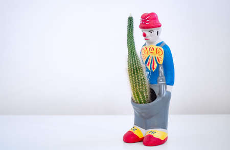 The concept of male potency. Ceramic flower pots in the shape of a clown. Cactus in a flower pot. The concept of male potency. Stock fotó