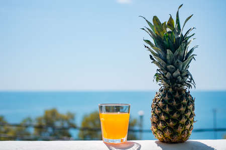 Fresh pineapple fruit. A glass filled with juice against the backdrop of the sea. Healthy food.