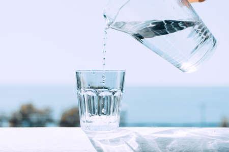 Reines Wasser aus einem Krug wird in ein Becherglas gegossen. Glas mit Wasser auf dem Hintergrund des Meeres. Gesunder Lebensstil.