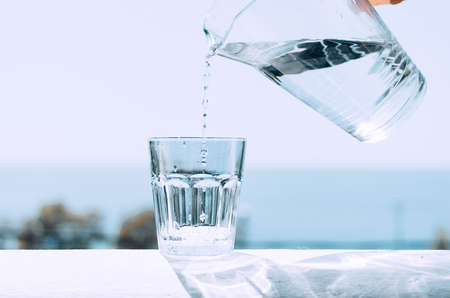 Se vierte agua pura de una jarra en un vaso de precipitados de vidrio. Vaso con agua en el fondo del mar. Estilo de vida saludable.