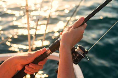 Female hand holding a fishing pole against the background of the sea. Sea fishing. The woman is fishing.