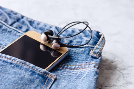 Headphones and smartphone in the pocket of jeans. Smart phone in the pocket jeans.