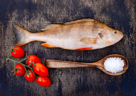 Fresh raw fish on a dark wooden background. River perch and spices Imagens