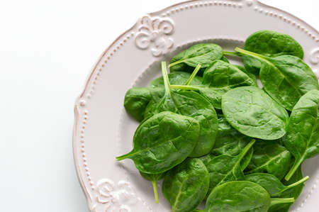 Young leaves of spinach on a plate. Top view, white background, copy space. Detox, a dietary food ingredient - green organic spinach