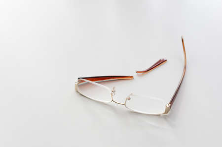 Broken glasses on a white background. Broken earband from the glasses