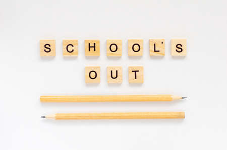 School's out. The inscription in wooden letters on a white background. Pencils on a white background