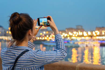 A young girl takes pictures of a night city with a cell phone camera.