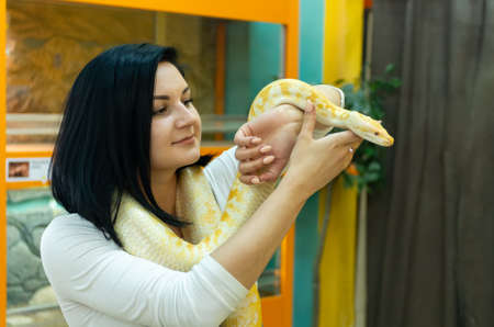 Beautiful brunette girl holding a python in her hands