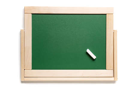 A piece of white chalk on the background of the school green board. View from above. Place for text.