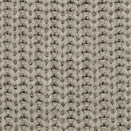 The texture of the knit fabric is beige. Close-up. Abstract background Archivio Fotografico