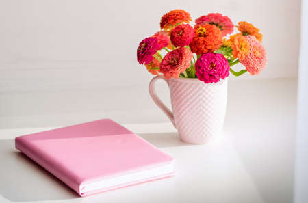 Female desktop. Pink notebook and a bouquet of flowers. Home office concept. 免版税图像