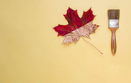 Brush and maple leaf on a yellow background. Autumn concept, flat lay. Copy space. Фото со стока