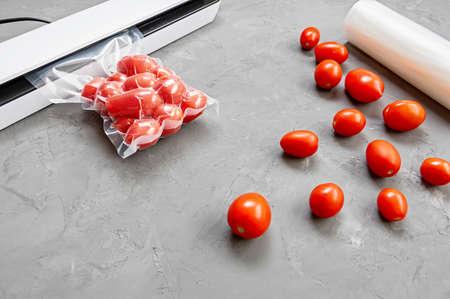 Plastic sealing machine. Vacuum packaging of fresh tomatoes.