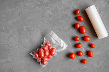 Vacuum packaging of fresh tomatoes. Flat lay.