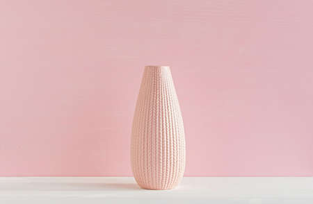 Ceramic vase on a pink background. Close-up. The concept of minimalism.