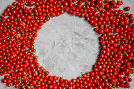 Round frame of cherry tomatoes on a gray background. Flat lay. Copy space. Фото со стока