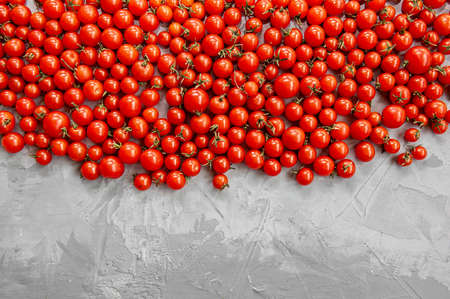 Cherry tomato pattern on a gray background. Flat lay, top view. Фото со стока