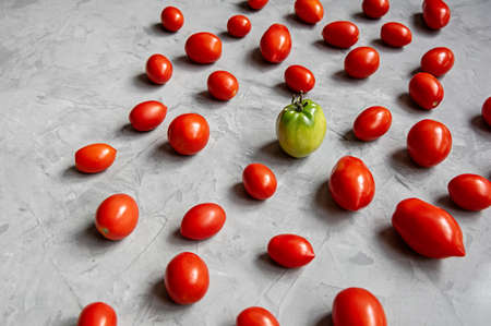 Red tomatoes and one green tomato on a gray background. The concept of uniqueness.