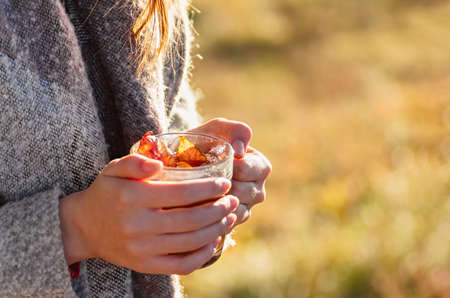 Cozy autumn. A cup of tea in female hands against the backdrop of an autumn landscape.