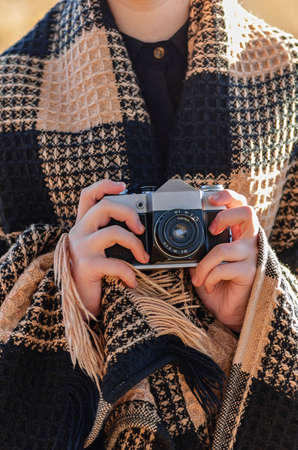 Outdoor photoshoot. The girl is wrapped in a warm checkered plaid and is holding a vintage camera in her hands. Close up.