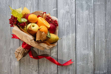 A delicious and beautiful bouquet of fruits. Autumn wedding. The brides bouquet. Wood background.