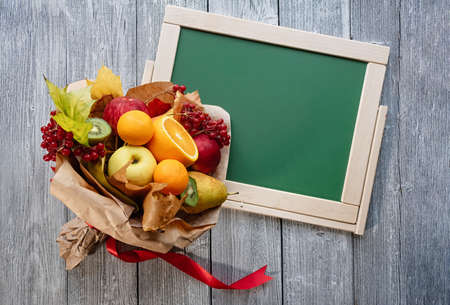 Unusual tasty fruit bouquet. Teachers Day. Copy space. Green school board on a wooden vintage background. Фото со стока