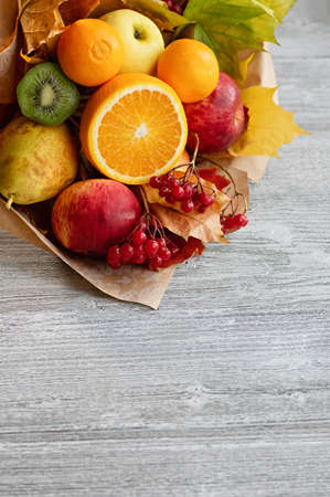 A delicious bouquet of ripe fruits. Harvest concept. Autumn composition. Copy space. Gray wooden background.